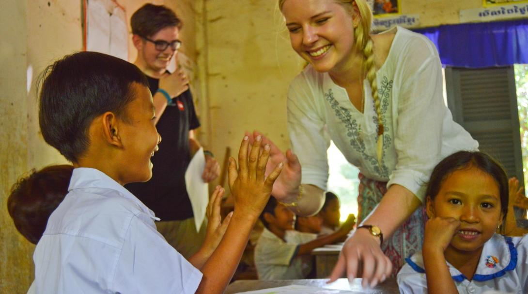A young child gets a high five from a Projects Abroad volunteer working with children in Cambodia at a local kindergarten.